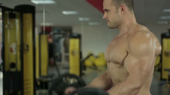 Thumbnail for Strong Muscular Man Exercising With Barbell, Looking in Mirror During Workout