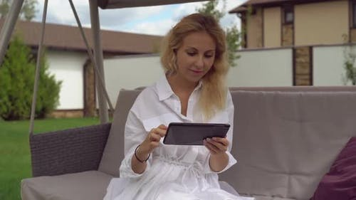 Businesswoman Sits in Backyard