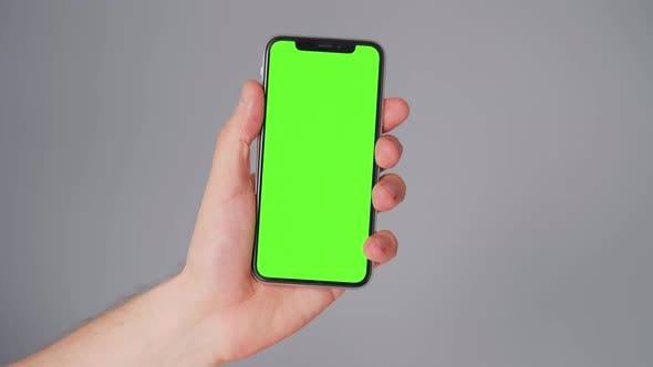 Thumbnail for Male Hands Using a Smartphone with a Green Screen on a Gray Background. Chroma Key