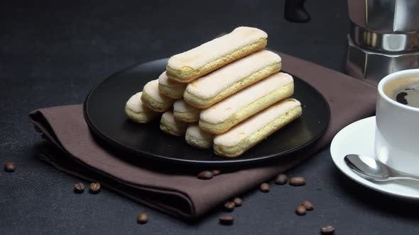 Cover Image for Italian Savoiardi Ladyfingers Biscuits and Cup of Coffee on Concrete Background