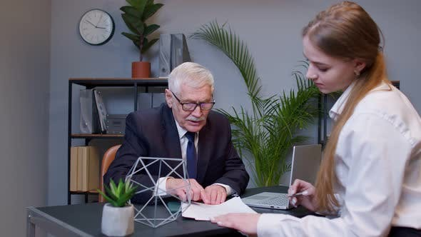 Senior Businessman Company Entrepreneur Ceo Examining Financial Data with Young Woman Colleague