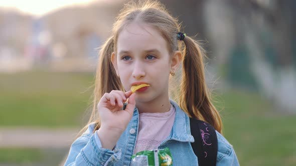 Young School Girl Eating Chips From Packet on Street