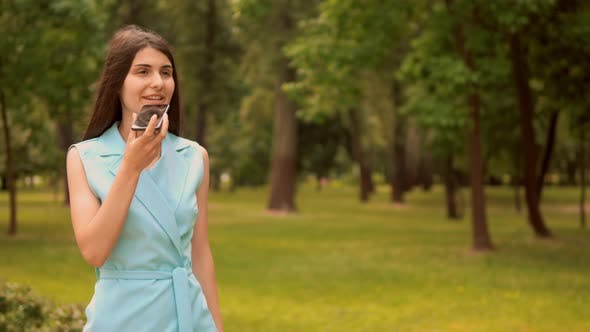 Thumbnail for Businesswoman Dictates Voice Message Walks Along Alley with Trees