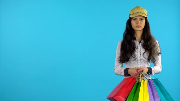 Thumbnail for Shopaholic Girl with Bags in Her Hands Is Standing and Starts Smiling. Blue Background