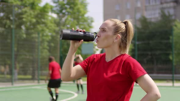 Cover Image for Young Female Soccer Player Drinking Water on Field