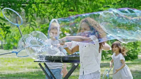 Thumbnail for Excited Kids Playing with Soap Bubbles in Park