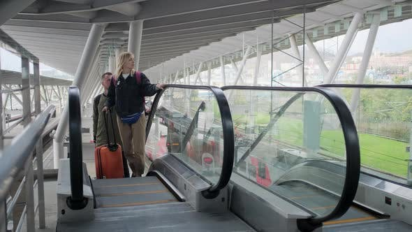 Traveling Couple on Airport Escalator with Baggage