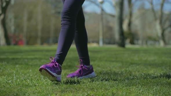 Thumbnail for Slim Female Legs in Black Leggings Walking on Grass in Park