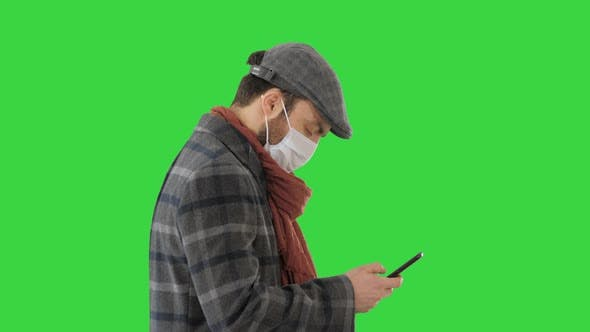 Thumbnail for Stylish Man in Medical Mask Walking and Using Smart Phone on a Green Screen, Chroma Key.