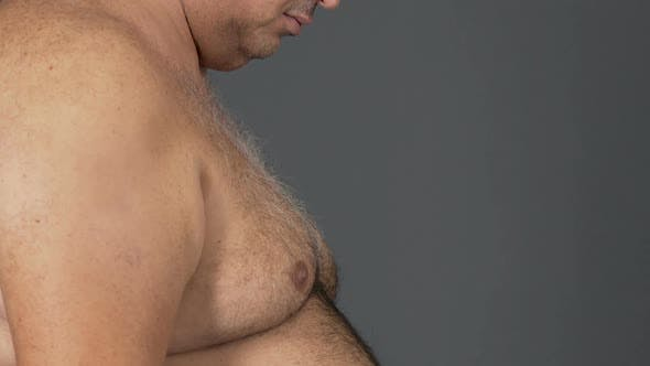 Obese fat male with big belly on grey background, diet concept, health care