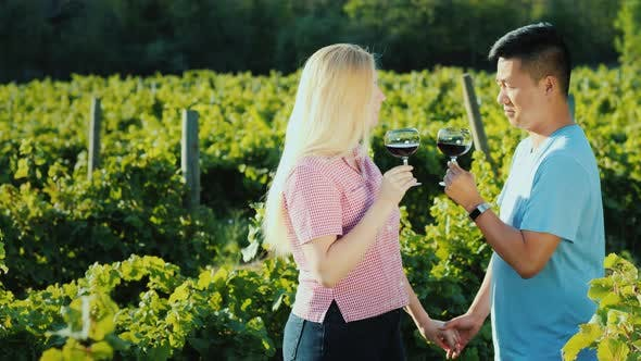 Multi-ethnic Couple in Love Tasting Wine in a Vineyard, Holding Hands. Honeymoon and Wine Tour