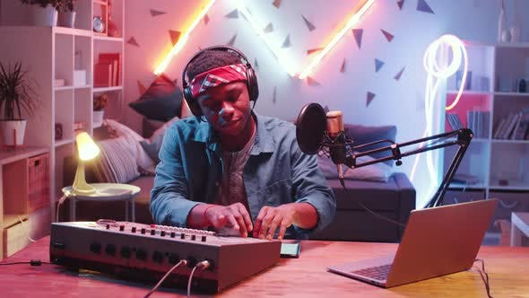 Thumbnail for Young Black DJ Using Mixing Console while Recording Music at Home
