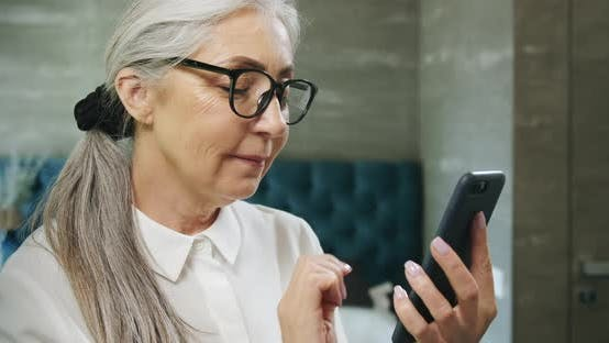Thumbnail for Aged Woman Texting on Smartphone