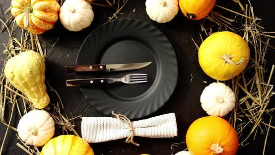 Thumbnail for Black Plate Surrounded By Yellow Pumpkins