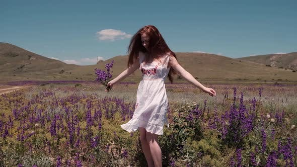 A Caucasian Beautiful Wonan Dancing on the Beautiful Field During Summer Day