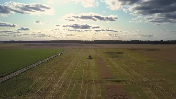 Thumbnail for Aerial View Harvester Drives on Endless Green Striped Field