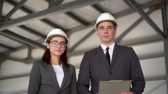 Thumbnail for Young Man and Woman in Helmets at a Construction Site. Businessmen in Suits Are Looking at the
