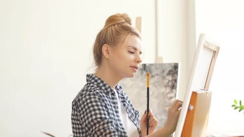 Funny Blond Girl with a Brush in Her Hand Using Spatula To Correct Her Art Work