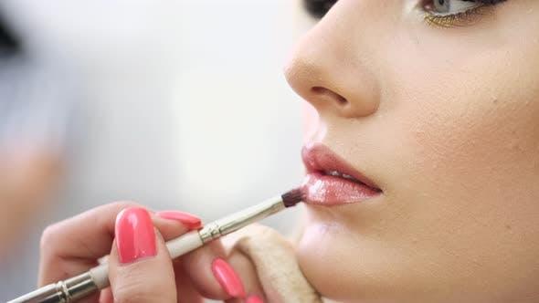 Thumbnail for Closeup Makeup Artist Applying Cosmetics on Woman's Lips