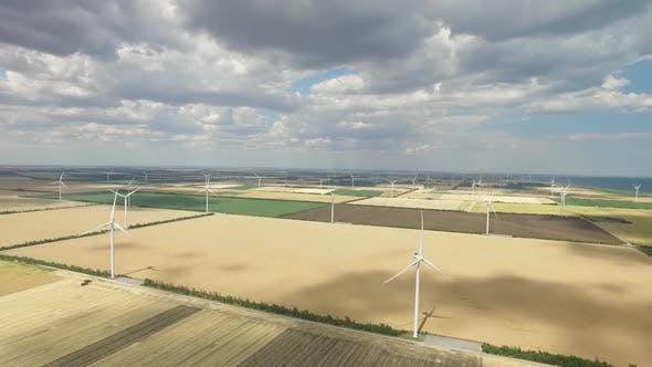 Wind Farms in Rural Areas Against the Background of Agricultural Fields Under a Blue Sky. Aerial