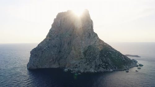 Sunlight Behind Tall Cliff in the Middle of Ibiza Ocean Waters