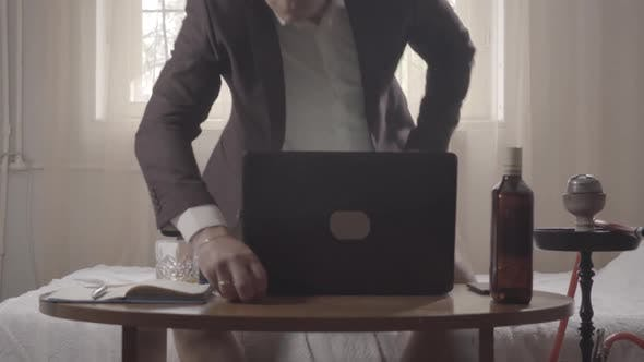 Relaxed Man in Underwear and Business Jacket Sitting Down in Front of Laptop and Turning on Wireless
