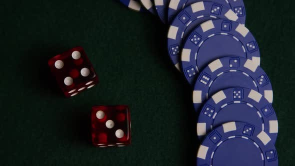 Rotating shot of poker cards and poker chips on a green felt surface - POKER 053