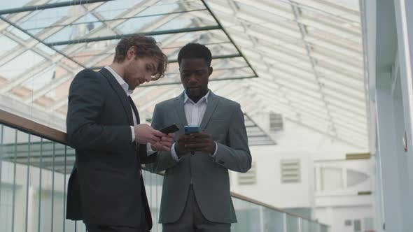 Two Businessmen Talking and Using Cellphones