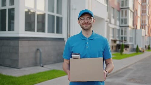 The Bespectacled Delivery Guy Looking at the Camera Smiles