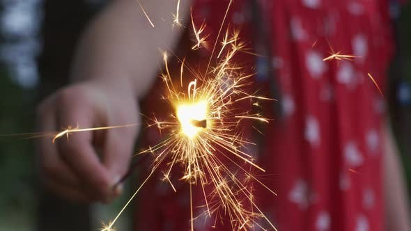 Thumbnail for Closeup shot of girl holding sparkler fireworks at 4th of July celebration.