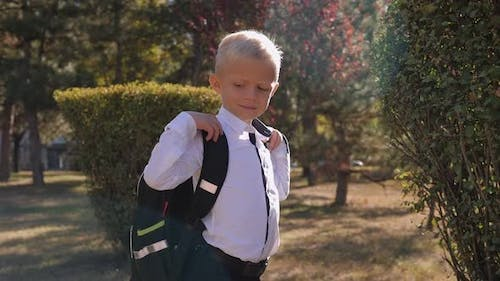 A Schoolboy in a Shirt with His Arms Crossed Over His Chest with a Backpack
