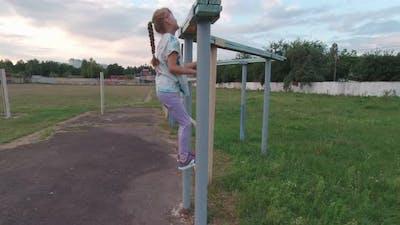 Girl Climbs On Sport Bar