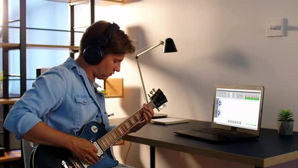 Man Playing Guitar and Recording Music at Home