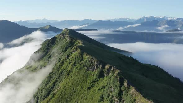 Drone View of Thick Cloudy Mist Surrounding the Lush Mountaintop with Sunny Sky