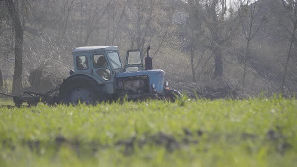 Thumbnail for Old Blue Tractor Riding Along Green Grass on Sunny Spring Day