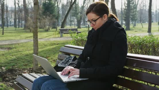 Thumbnail for Woman working on laptop in the park