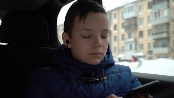 Thumbnail for Young Boy Using Smartphone During Taxi Ride in City