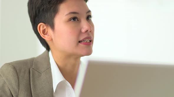 Thumbnail for Asian business woman smiling and talking to colleague