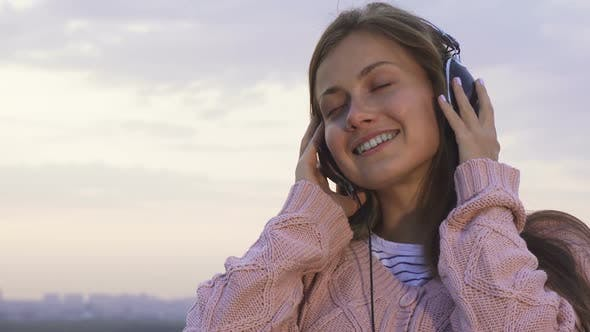 Thumbnail for Happy Girl Listening To Music with Headphones Standing on the Roof