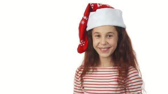 Thumbnail for A Girl in a Santa Claus Cap Smiles at the Camera