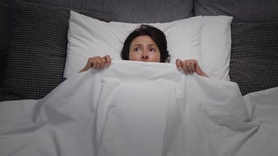 Scared Woman in Bed