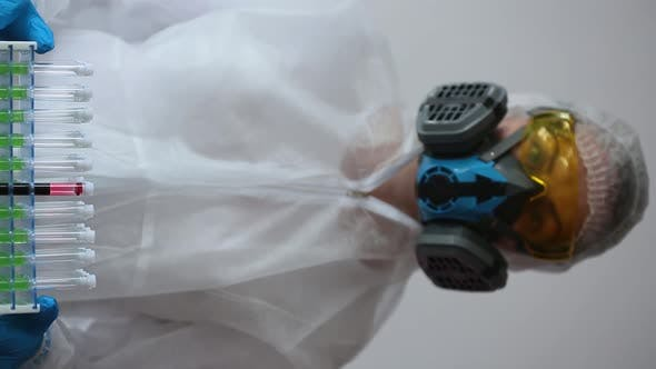 Thumbnail for Vertical Video. Doctor in a White Protective Suit and Respirator Showing a Test Tubes Holder with