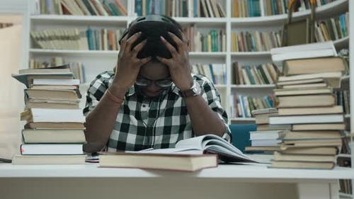 Stressful African Young Man Studying in Headphone