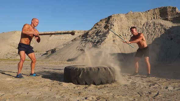 Thumbnail for Two Male Athletes Training Together Hit the Wheel with a Hammer at Sunset in the Mountains on the