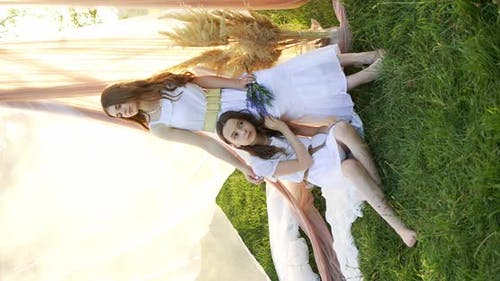 Two Girl Teenagers in White Dresses with Flowers Bouquet Posing on Chifon Background in a Field at