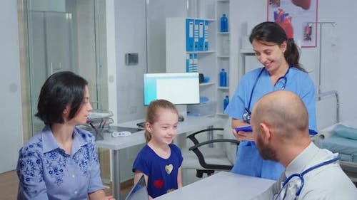Doctor and Nurse Talking with Child Patient