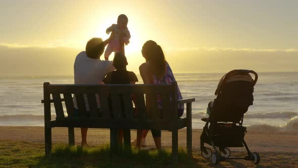 Happy Family Playing and Having Fun on the Beach at Sunset