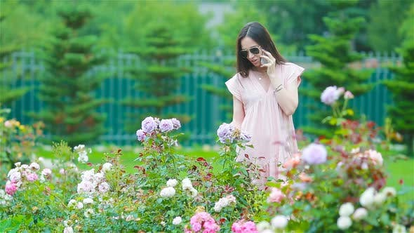 Thumbnail for Young Girl in a Flower Garden Among Beautiful Roses. Smell of Roses