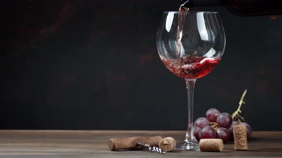Red Wine Is Poured Into the Glass. On a Black Background.