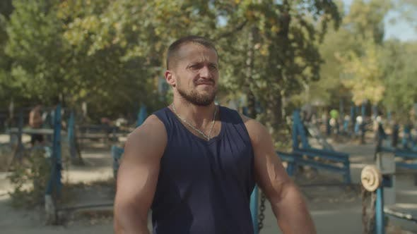 Thumbnail for Strong Athlete Flexing His Muscles in Outdoor Gym